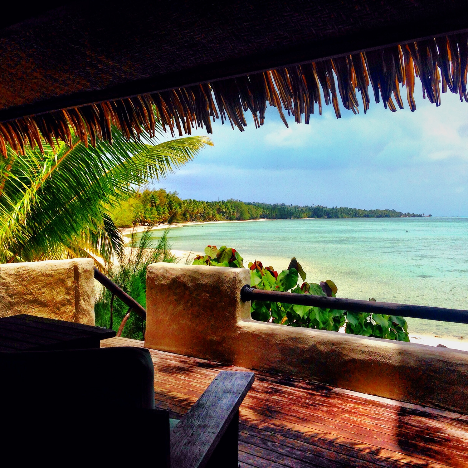 Looking out to pale blue waters from a shady cabana