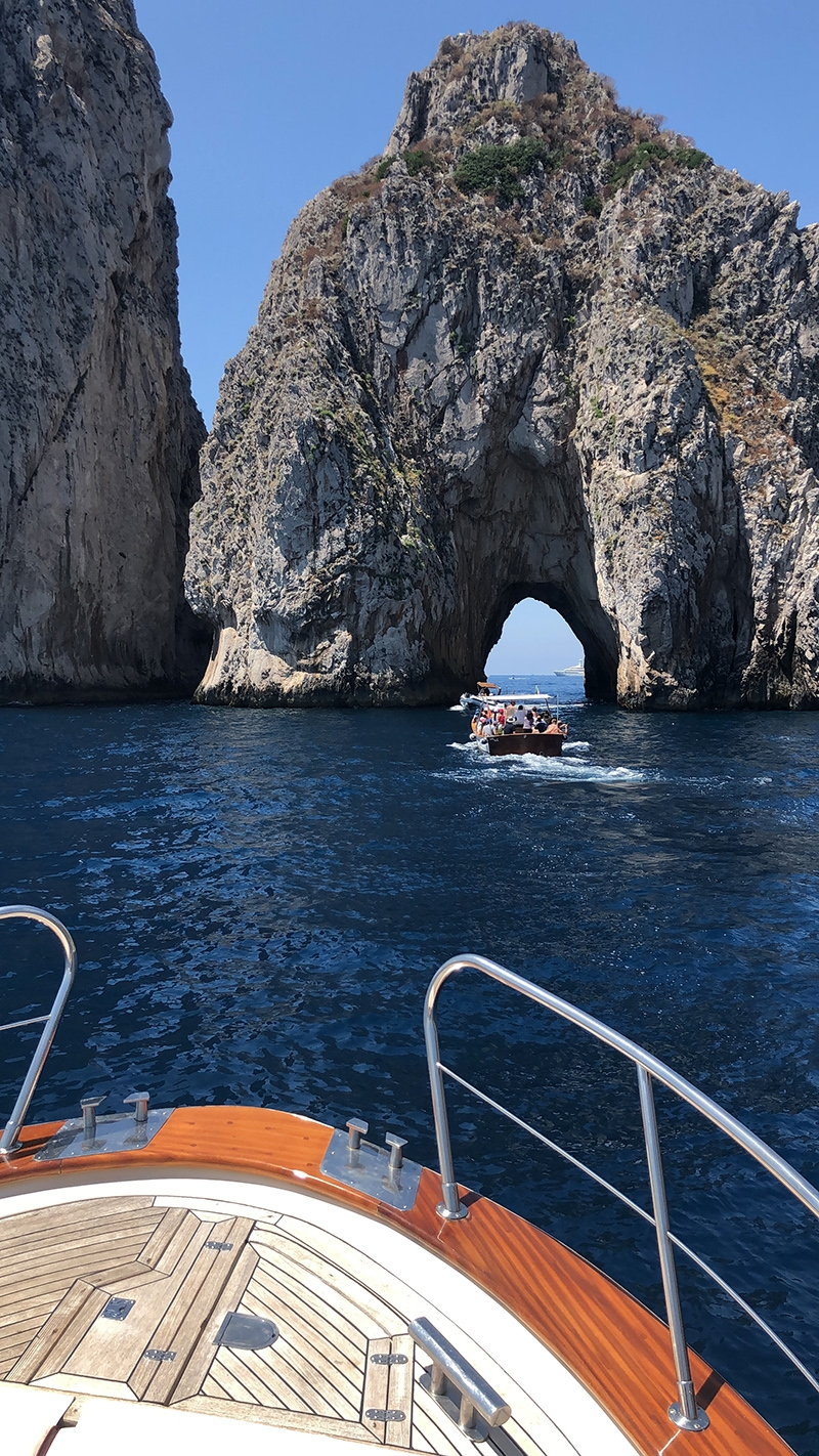 The view from the bow of a boat heading towards faraglioni rocks.