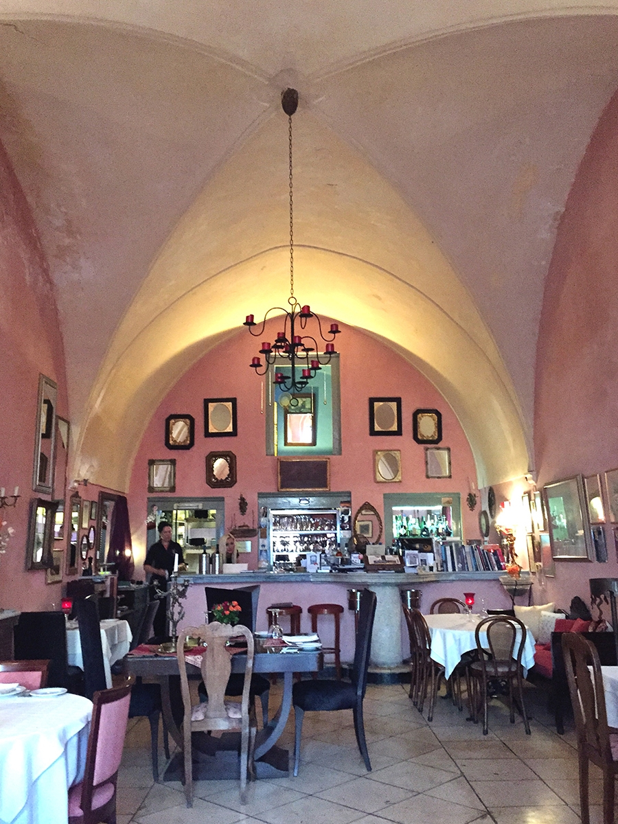 The interior of a restaurant in Santorini boasts structured arched roof detailing and pink walls