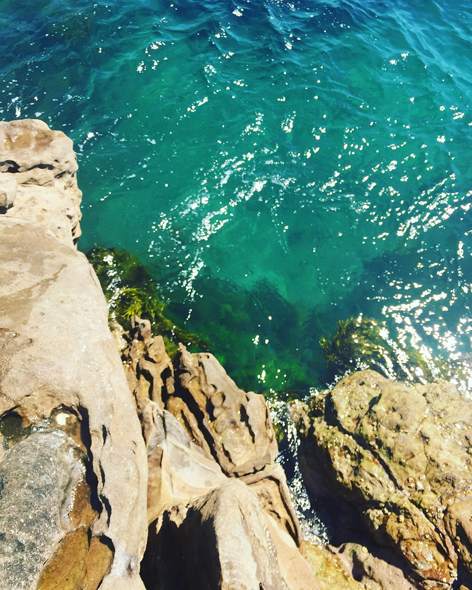 Looking down at the turquoise water from the top of large rocks
