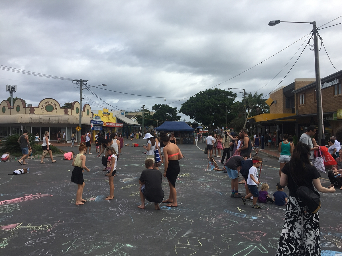 Locals drawing on the road with chalk at The Square in Byron Bay