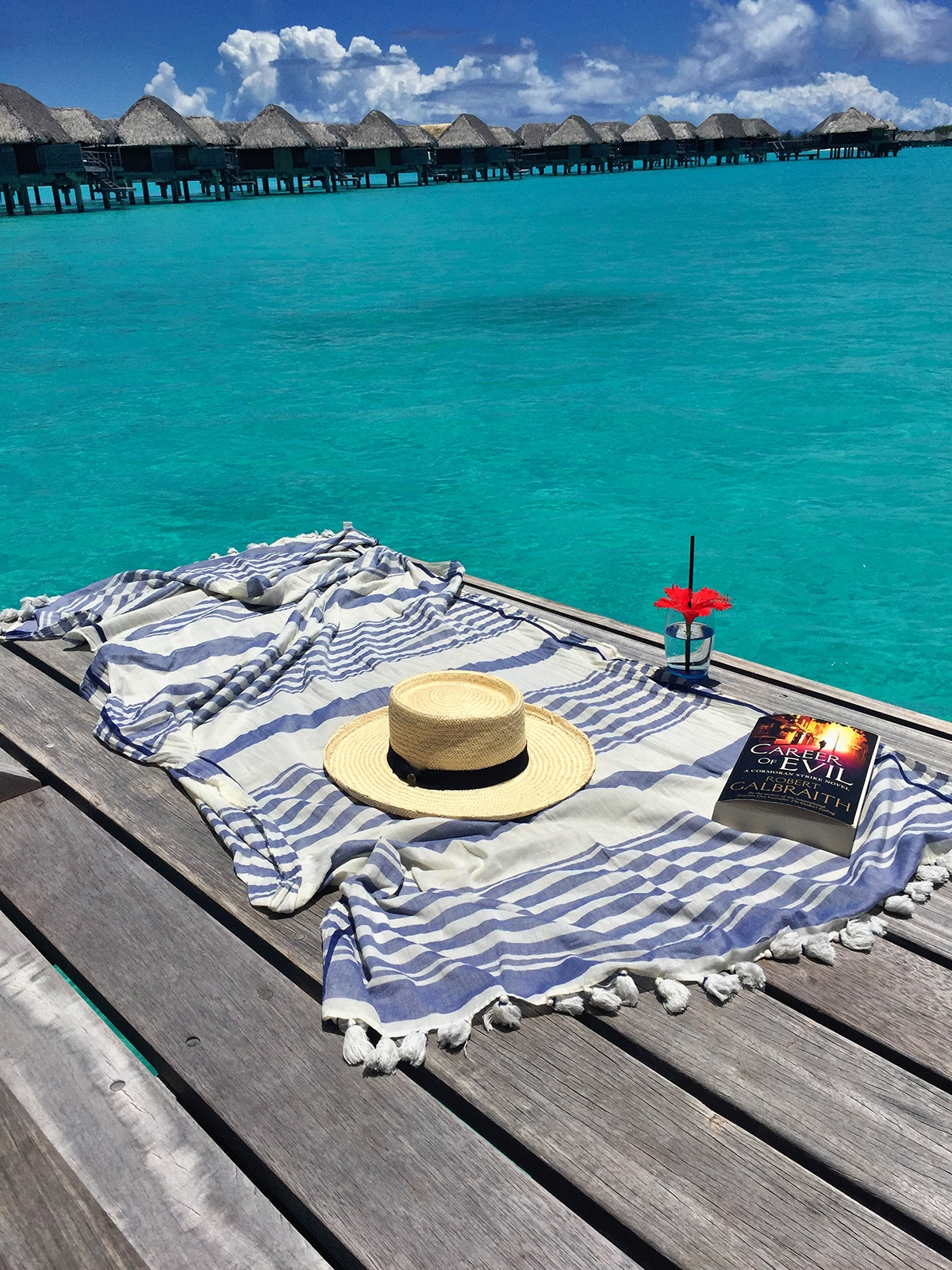 A towel, straw hat, book and glass of water sit on the floating wooden boardwalk and look out to the floating villas atop the bright blue ocean