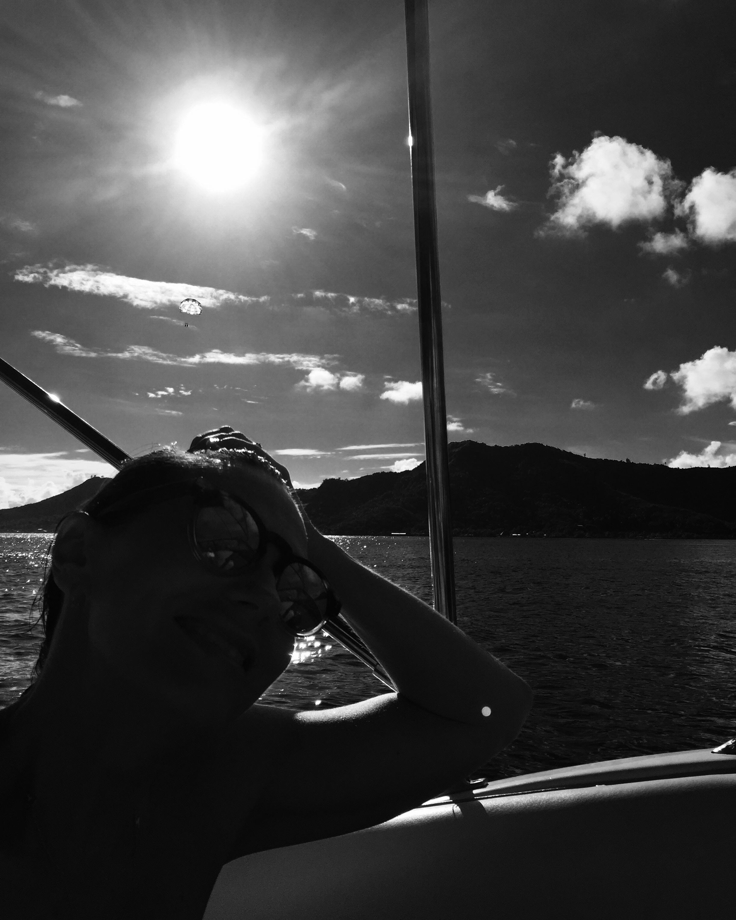 A black and white image of the silhouettes of a woman sitting on a boat and the Bora Bora landscape