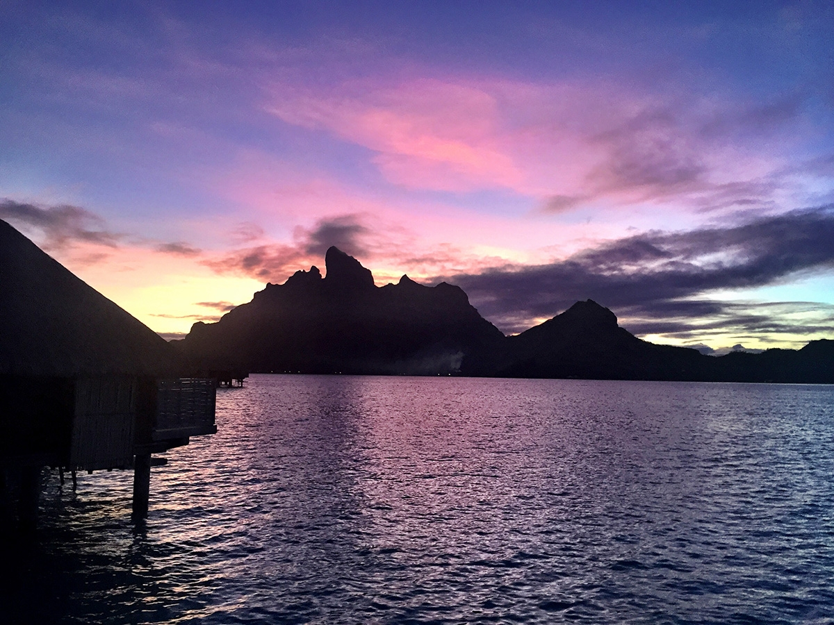 The sunset behind Mount Otemanu paints the sky and sea an array of pinks and purples