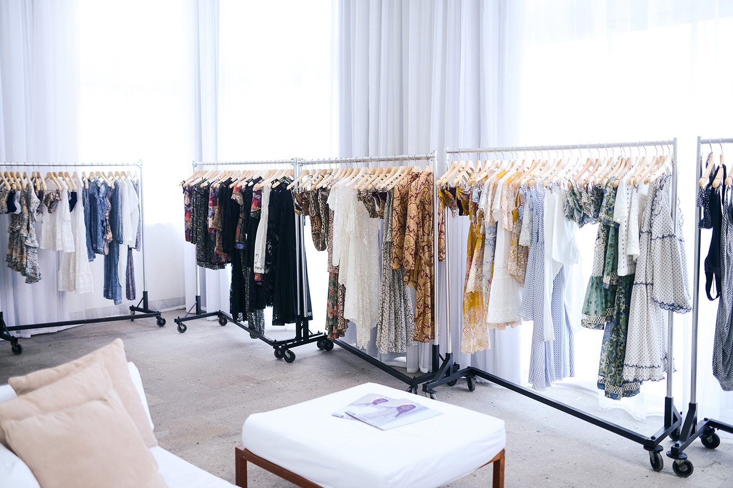 Racks of clothes are placed around the boarder of our bright white showroom at the Shore Club