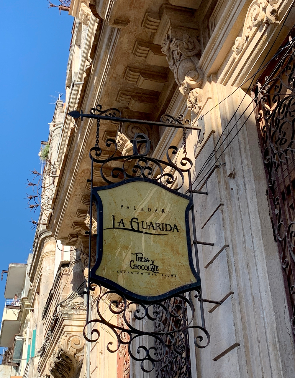 """A sign with wrought iron detailing on the exterior of a restaurant that reads, """"La Guarida"""""""