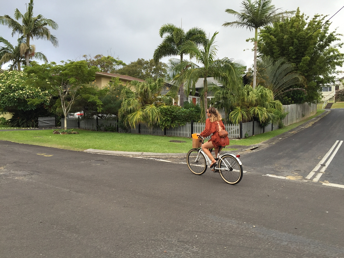 Marnie riding her bike through the quiet, green streets