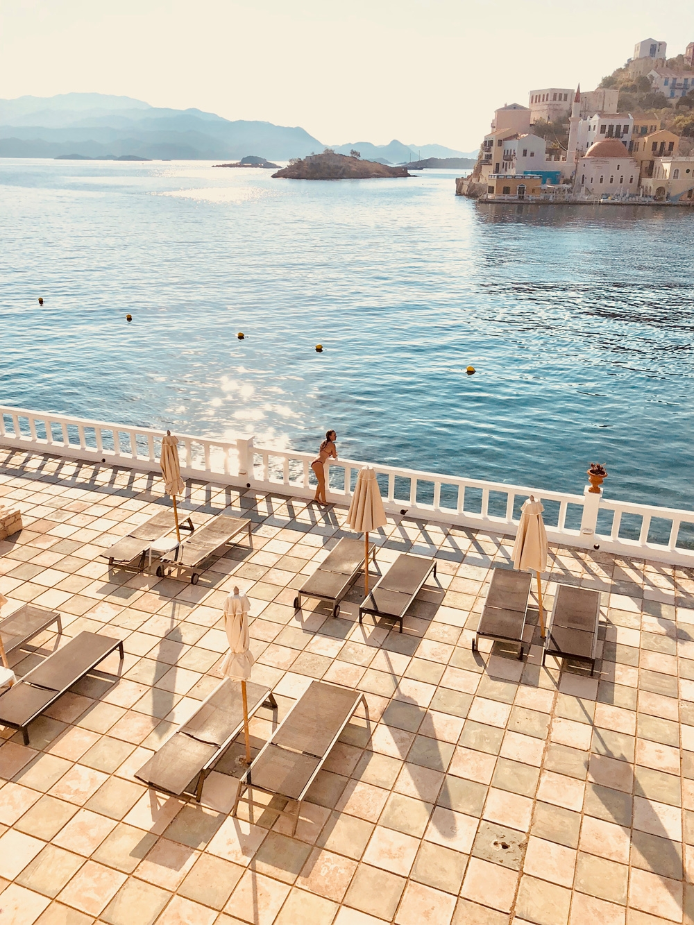A tiled balcony with sun loungers and umbrellas overlooking the sun kissed water of Kastellorizo