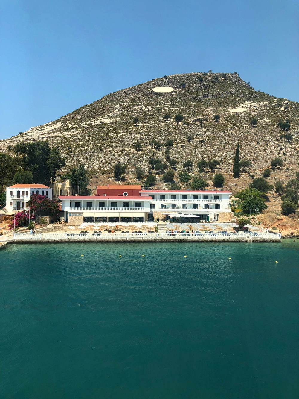 A view of the Megisti Hotel from the harbor. The long white building sits at the base of a mountain and offers sun loungers and umbrellas along the shoreline