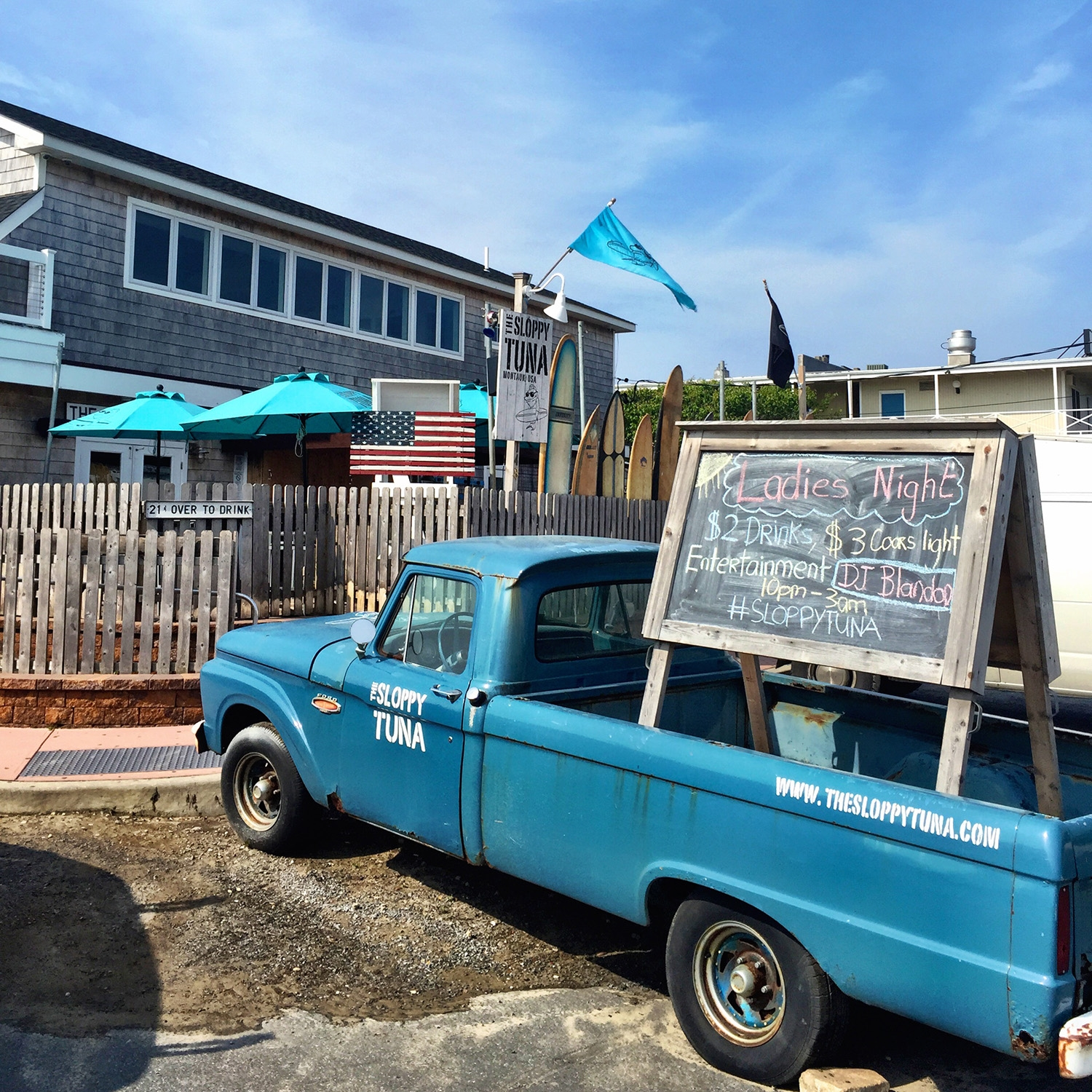 A blue pickup truck parked on the sidewalk in front of a shingle house has a large blackboard sign in the tray advertising a Ladies Night
