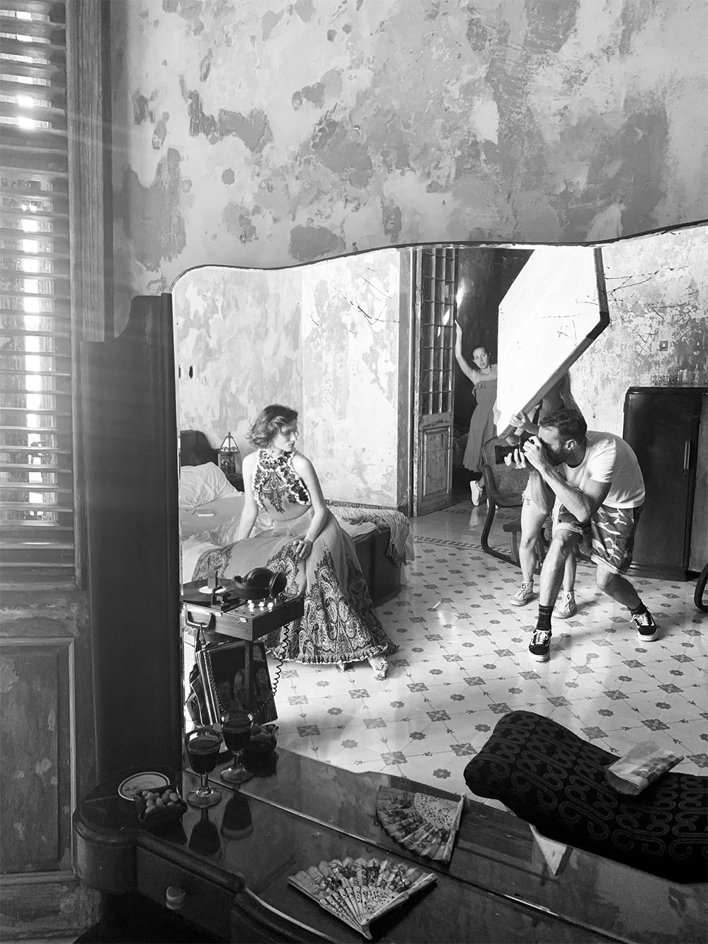 A black and white behind the scenes shot of Spring 19. In the reflection of an antique mirror, our model is being photographed while posing on the end of a bed