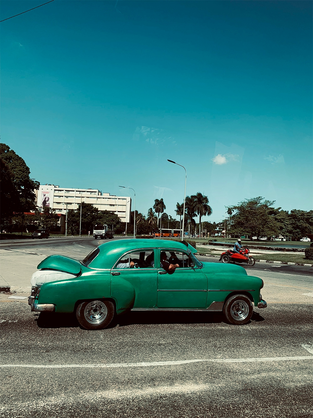 A vintage green car is parked on a quiet road in Havana