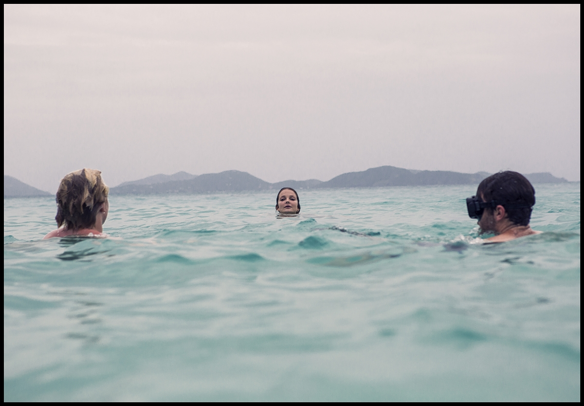 A behind the scenes shot of our model and team swimming in the ocean with large mountains in the background