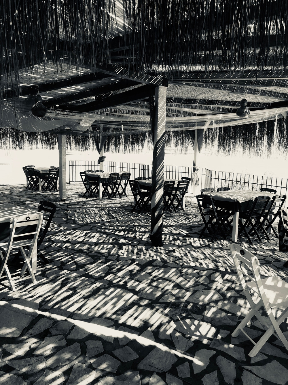 A black and white image of Saint George Beach Club displays wooden tables and chairs underneath a large straw roof next to the ocean