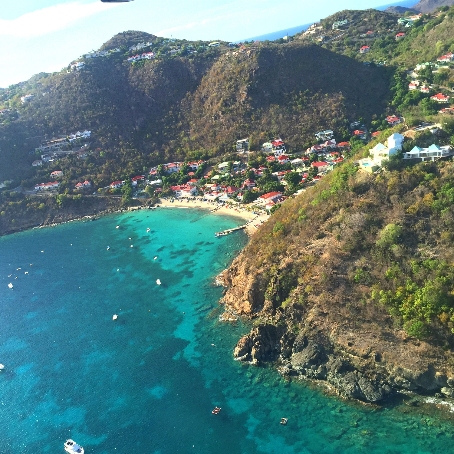 An aerial shot of rolling green hills, bright ocean and small township of St Barths below