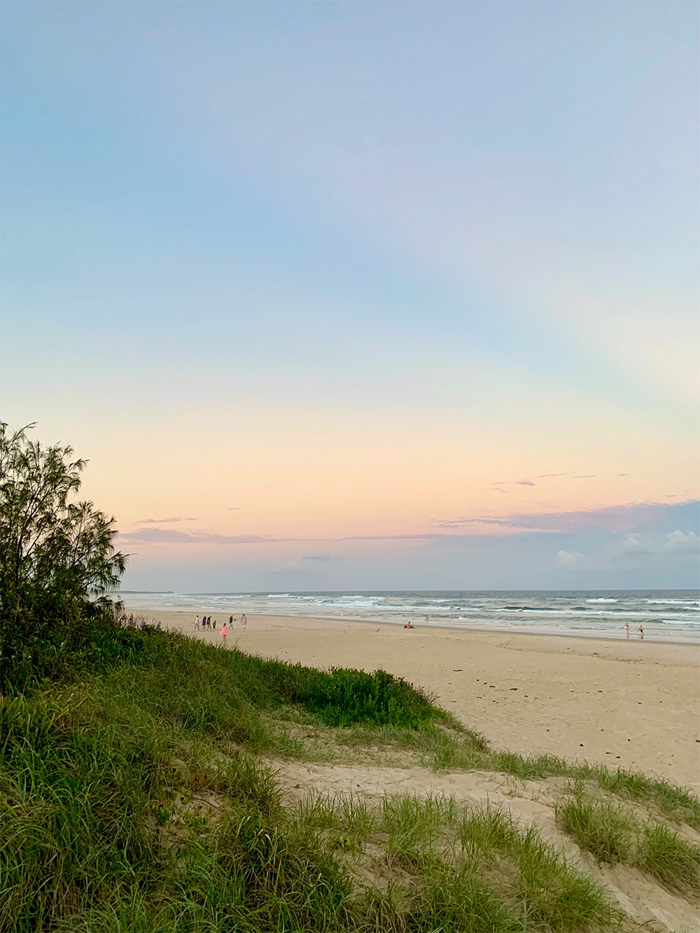 Groups walk along the sand and watch the dreamy summer sunset over the expansive beach