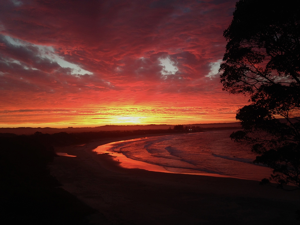 A moody, deep red sunset over the coastline of Byron Bay