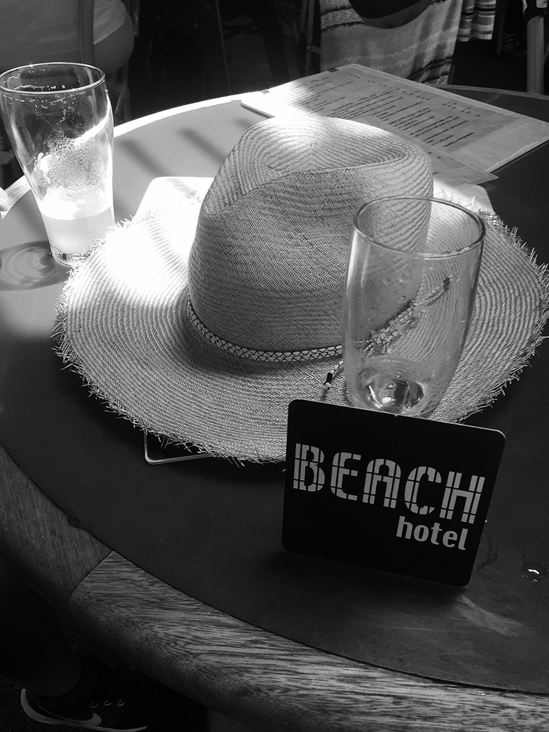 Two half full glasses and a straw hat sit on a table at The Beach Hotel