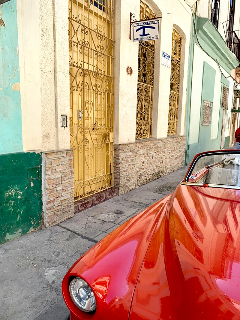 A red car parked on a street lined with colourful pastel buildings