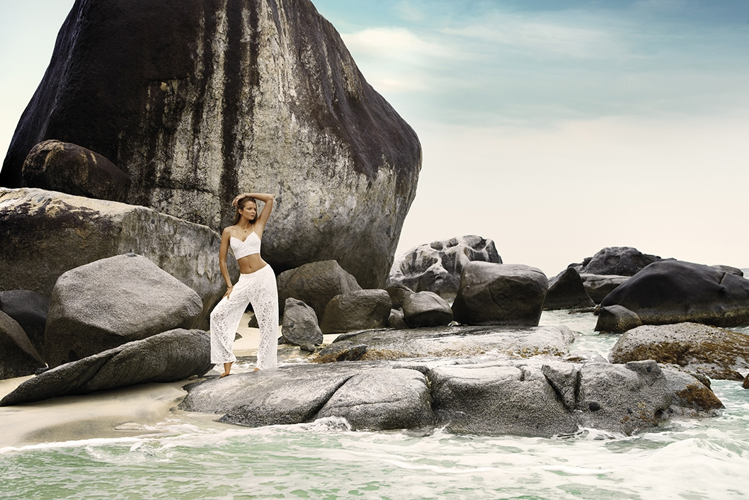 A campaign image of our model standing amongst large rocks on the shoreline