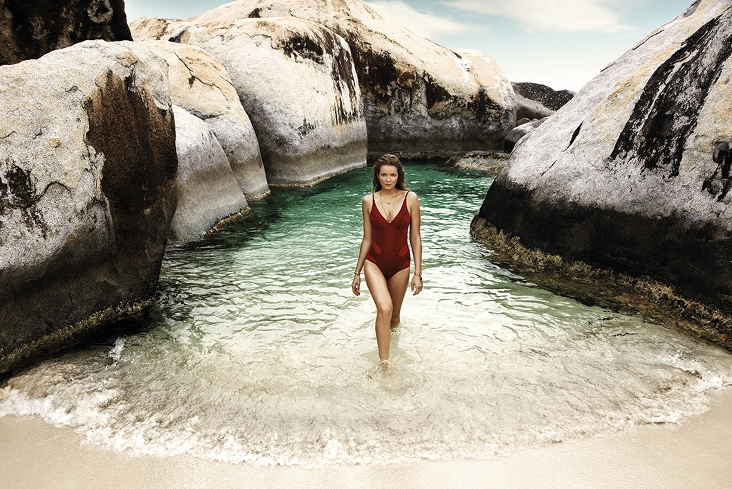 A campaign image of our model between large rock formations emerging from the water