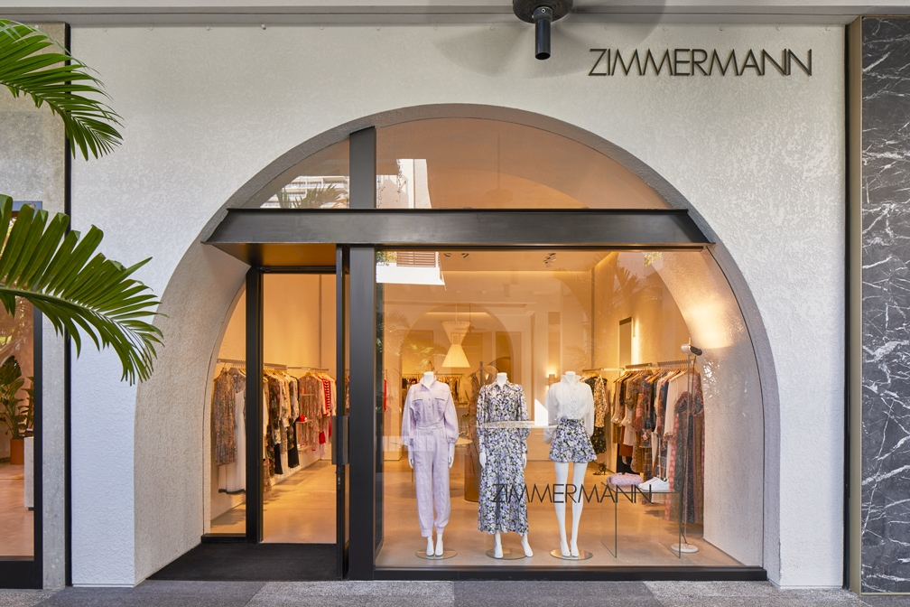 The storefron our our Zimmermann Bal Harbour store with clothing styles in the window and palm trees out front