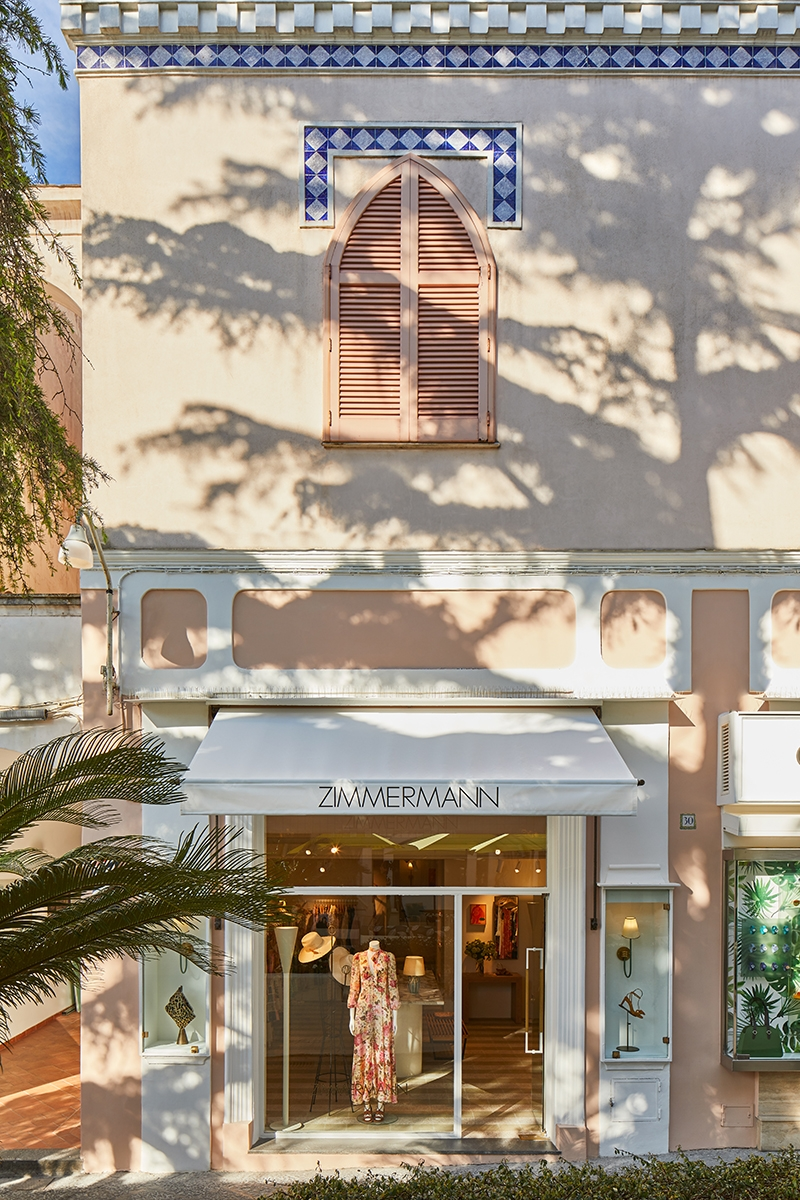 The exterior of our Capri boutique displays a muted apricot building with white finishes and blue tile detailing. A single mannequin stands in the window and two casings of accessories feature on both sides of the entrance.