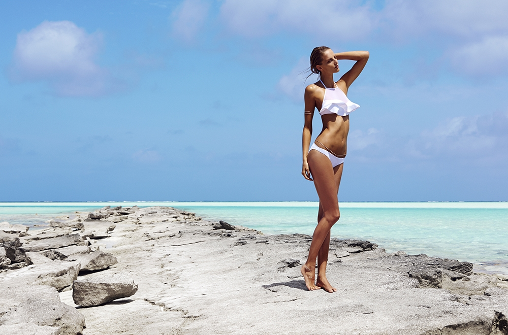 A Summer Swim 2014 Campaign image of our model standing on a large grey rock wearing a white bikini