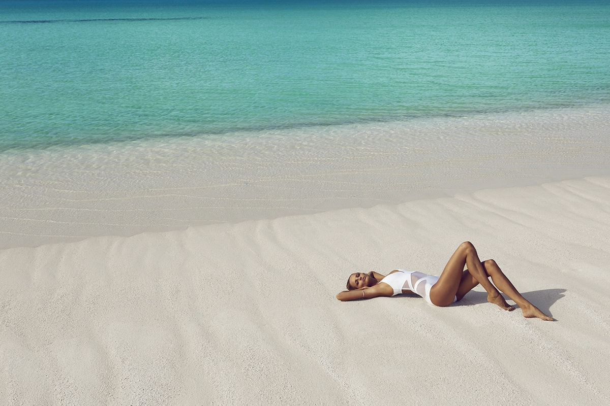 A behind the scenes image of our model laying along the water's edge on crisp white sands