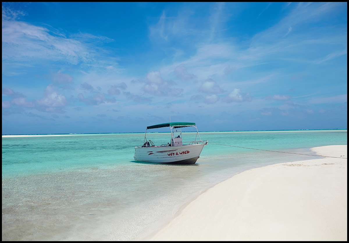 A single boat moored along crisp white sand and turquoise waters