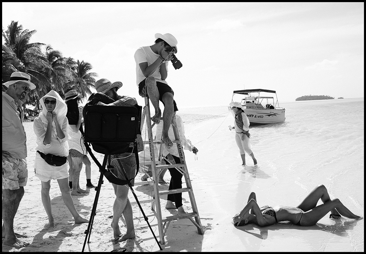 A black and white behind the scenes shot of a photographer perched atop a ladder shooting a model lying on the sand below