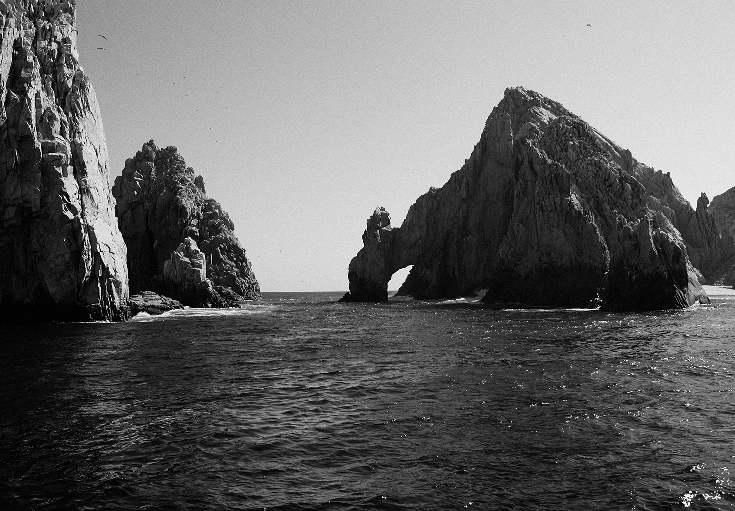 A black and white image of large sea stacks