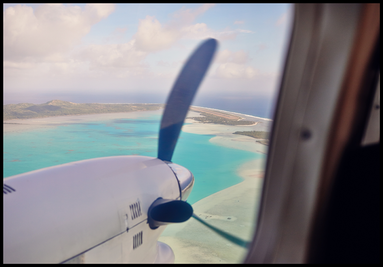 An aerial image of the Cook Islands, surrounding reefs and and seaplane propeller
