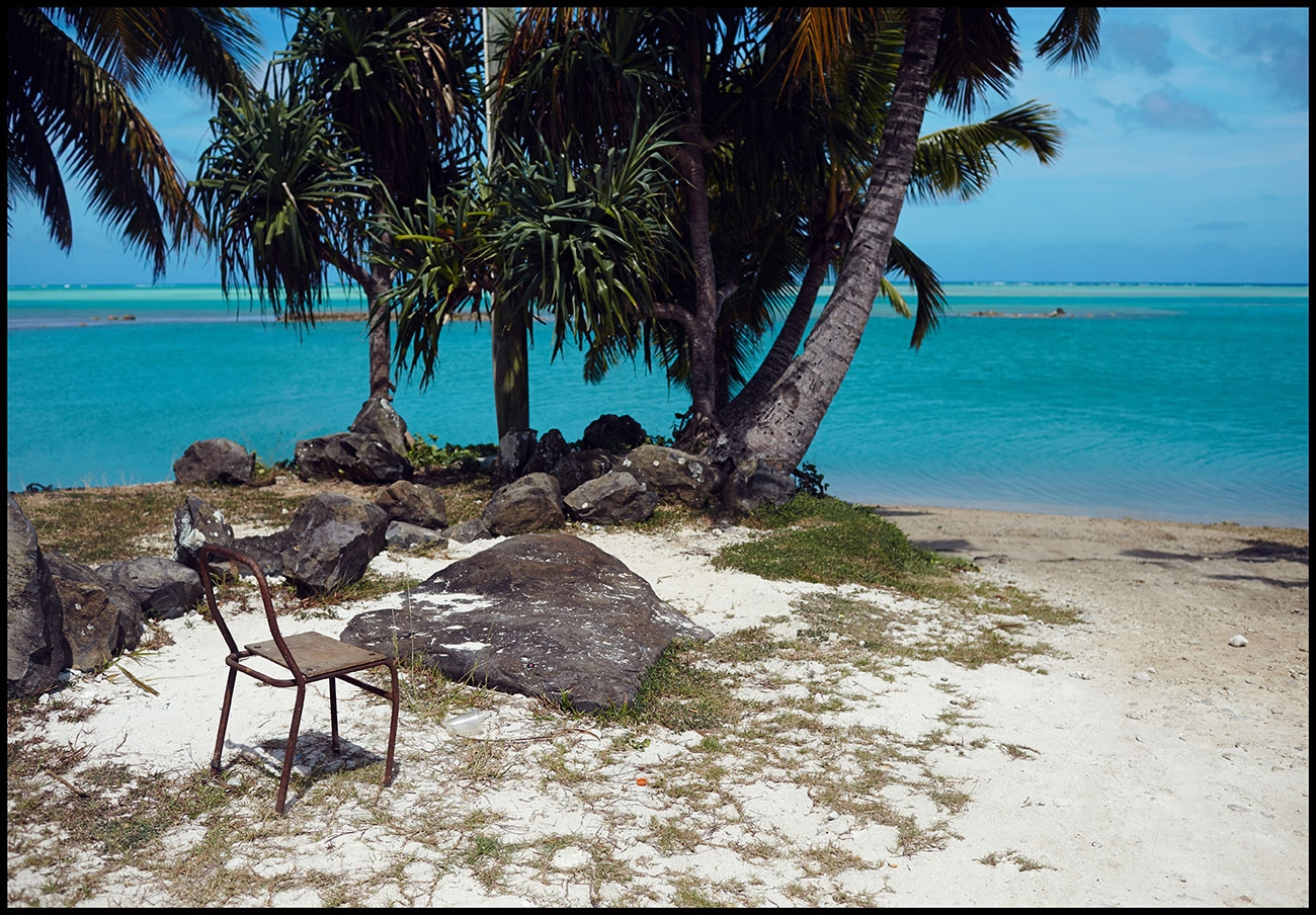 A single wicker chair sits along a palm tree lined beach looking out at the blue ocean of the Cook Islands