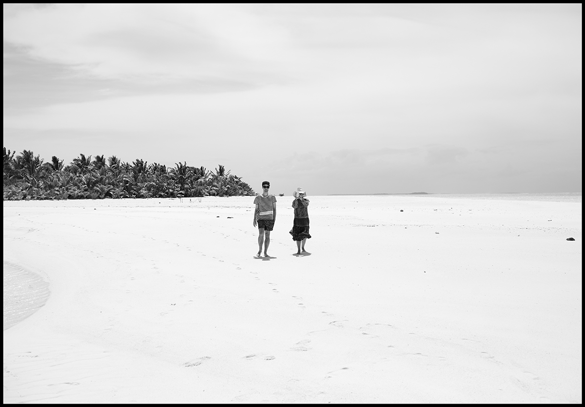 A black and white image of two people standing along expansive white sands, with tropical palms clustered in the background