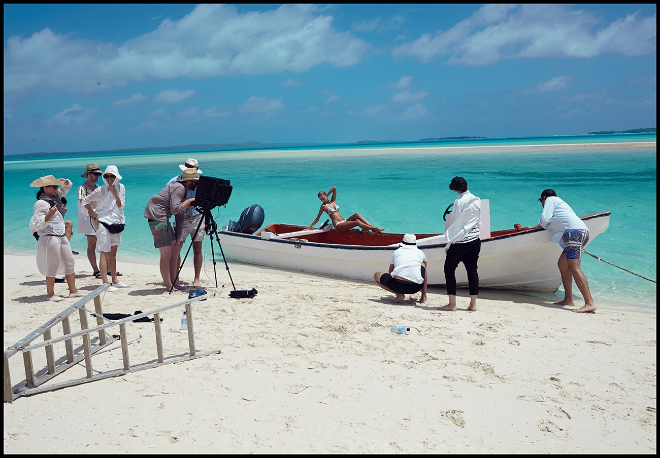 A behind the scenes shot of our model posing on a beached boat and the team shooting her