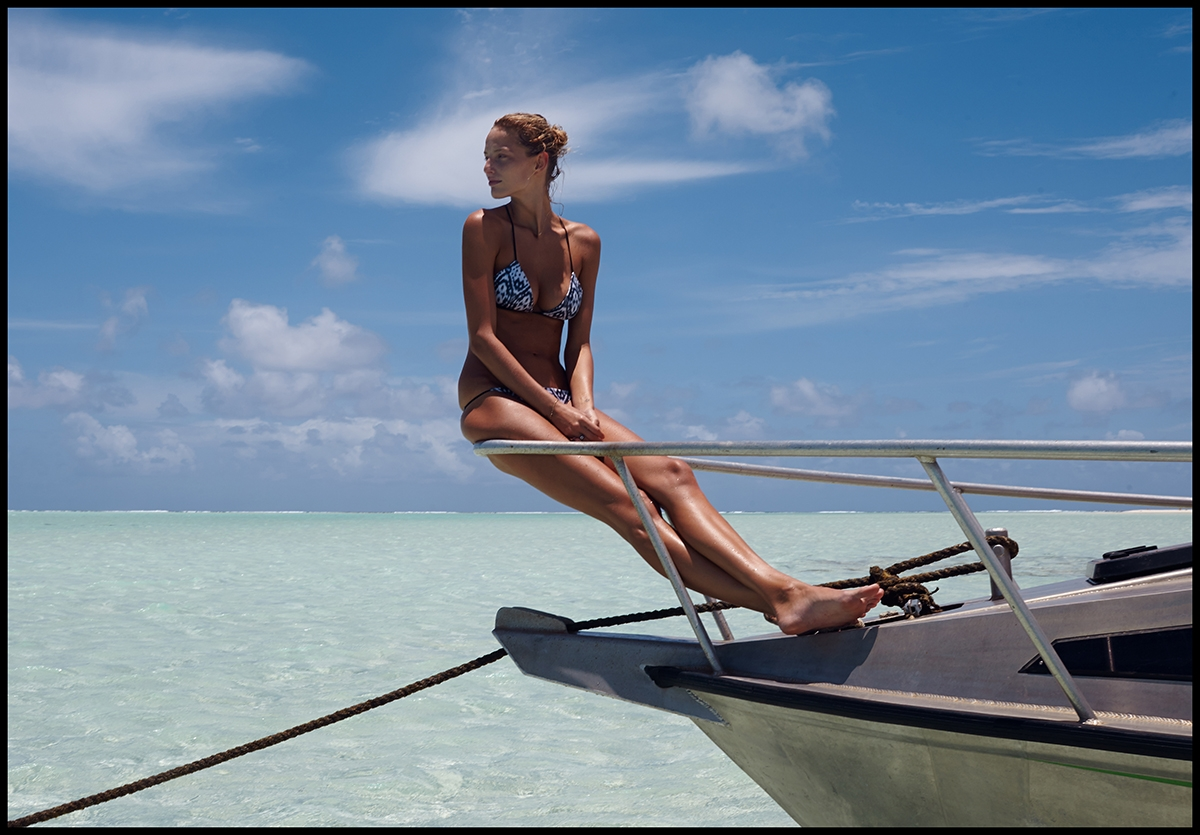 Our model is perched at the front of a white boat looking over her shoulder at the bright blue surrounding waters