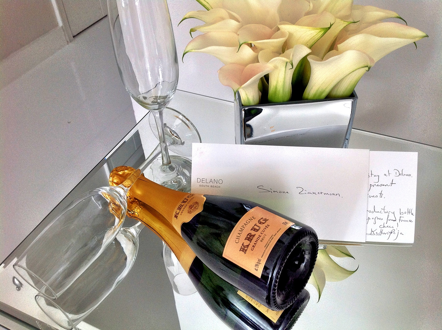 A bottle of champagne accompanied by flutes and flowers sits on a small table as a welcome gift