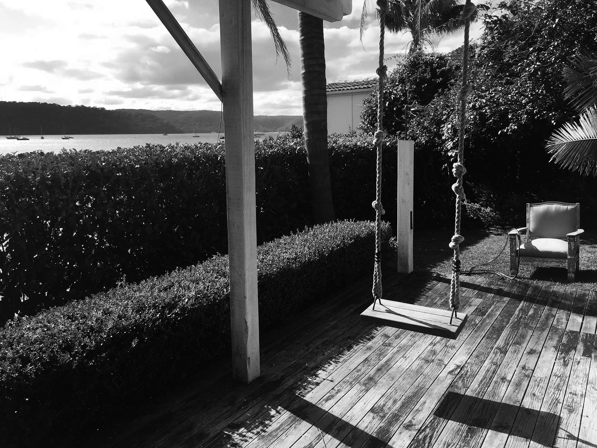 A black and white image of a swing hanging from the roof of Barrenjoey Villa, next to the water's edge