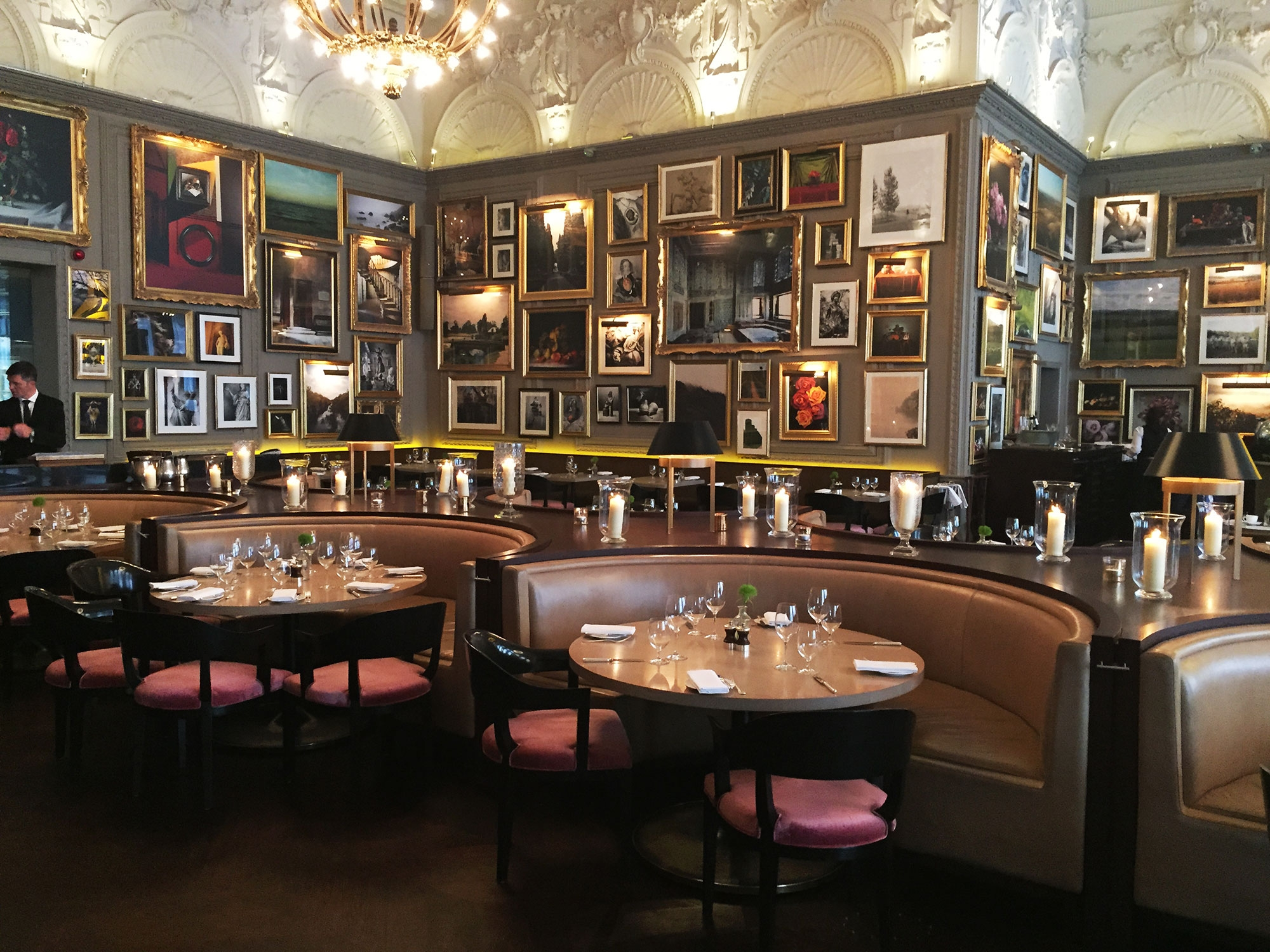 The interior of Berners Tavern contains framed pictures covering the walls and booth seating. June 2016