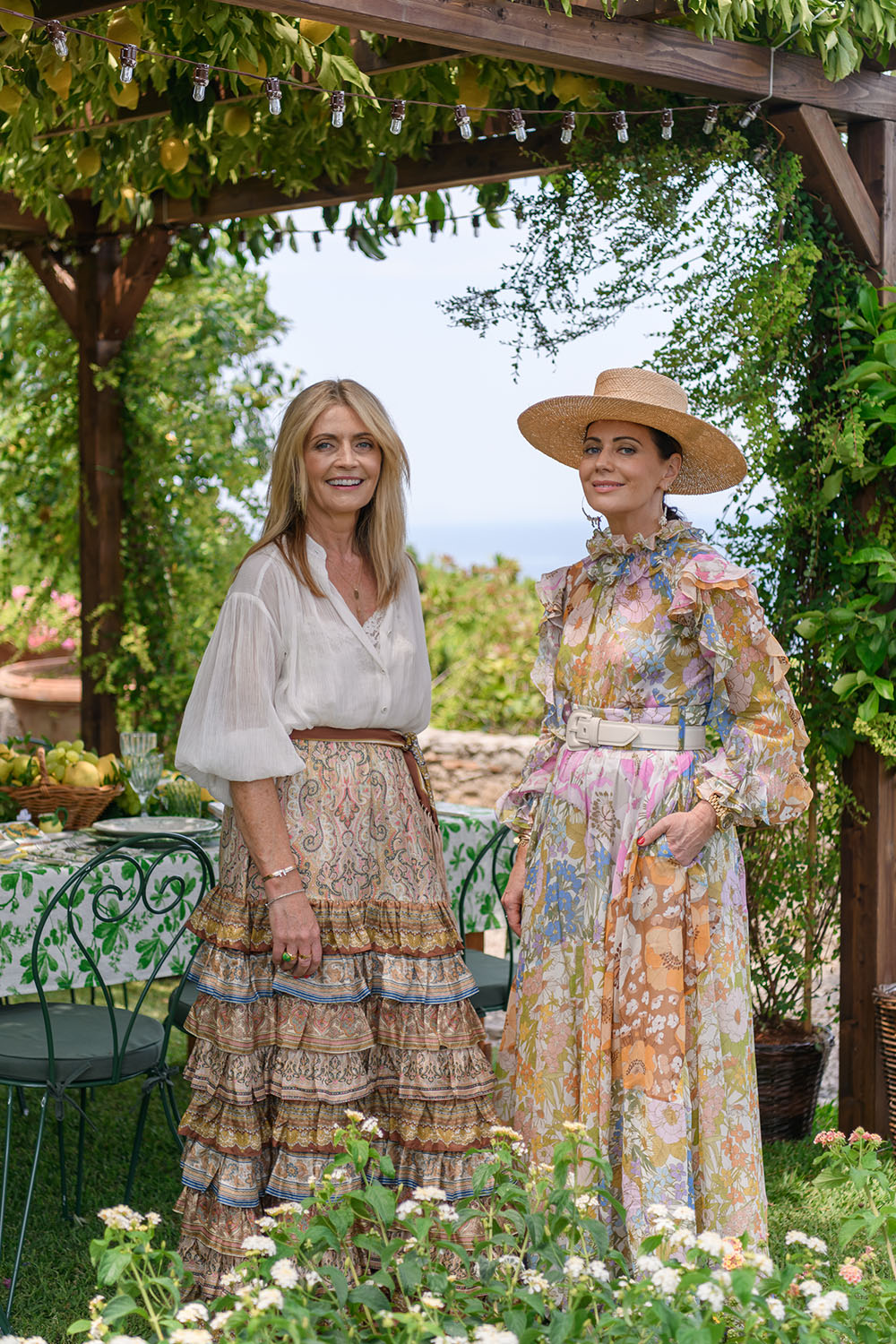 Simone and Nicky Zimmermann stand in a garden underneath a lemon trellis with a table set behind them.