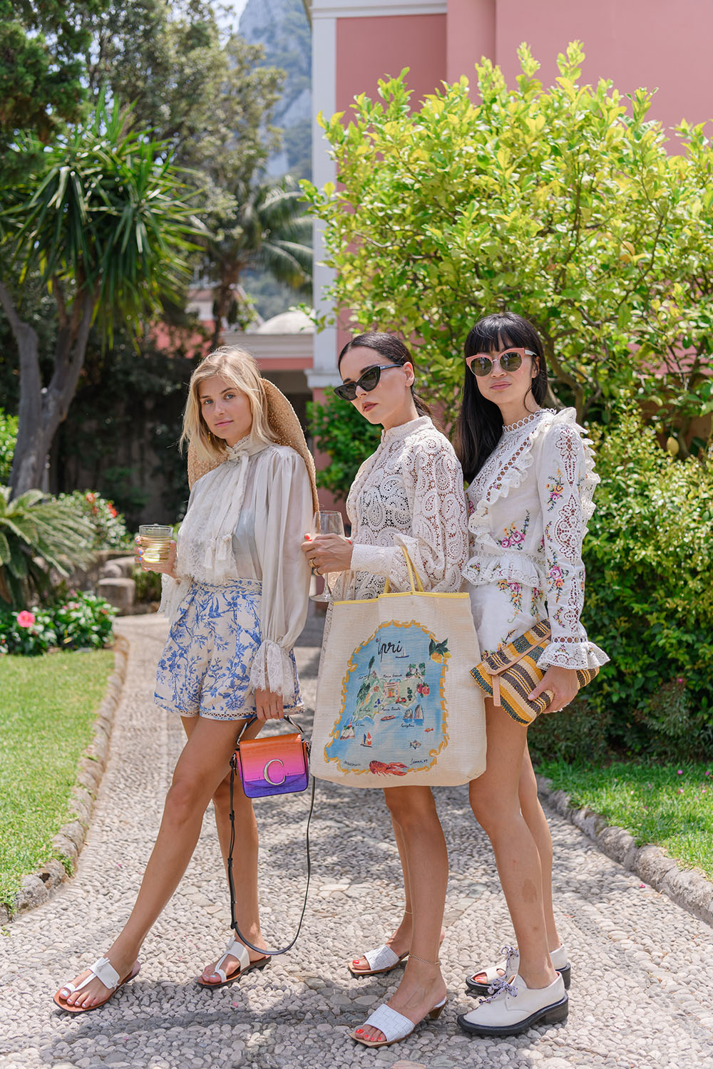 Xenia Adonts, Evangelie Smyrniotaki and Mimi Xu stand in a line on a cobblestone footpath dressed in Zimmermann.