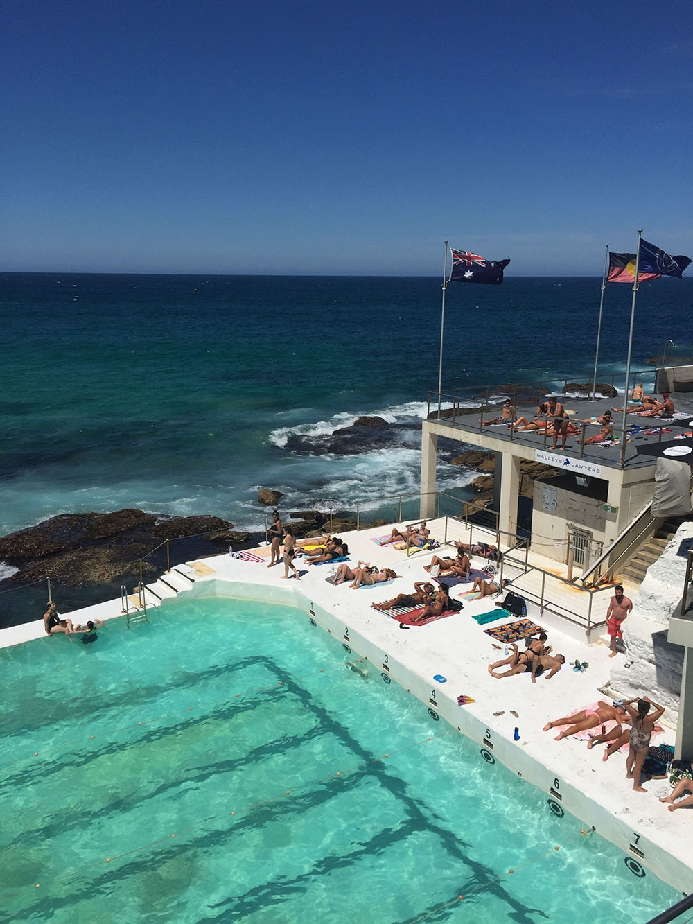 Clear skies, blue water and sunbathers at Bondi Icebergs, April 2016