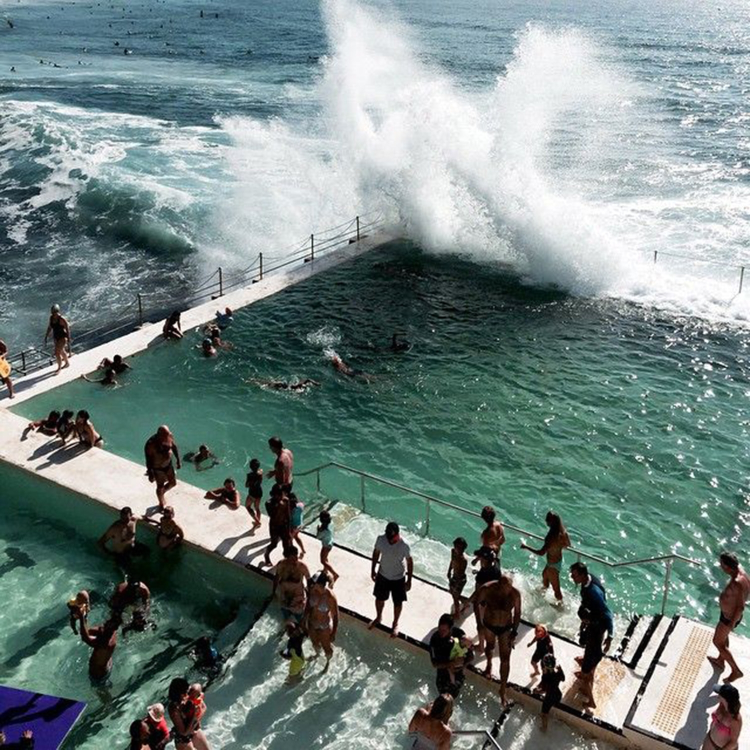 The waves crash against the Bondi Icebergs as people line the pools