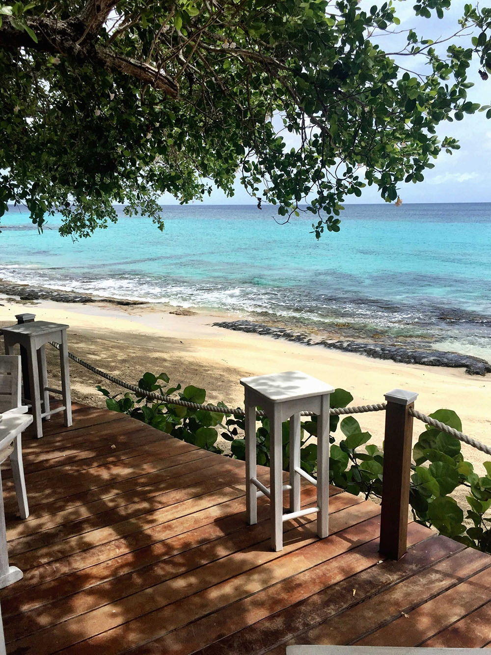 Sitting on a wooden verandah by the Mustique shoreline