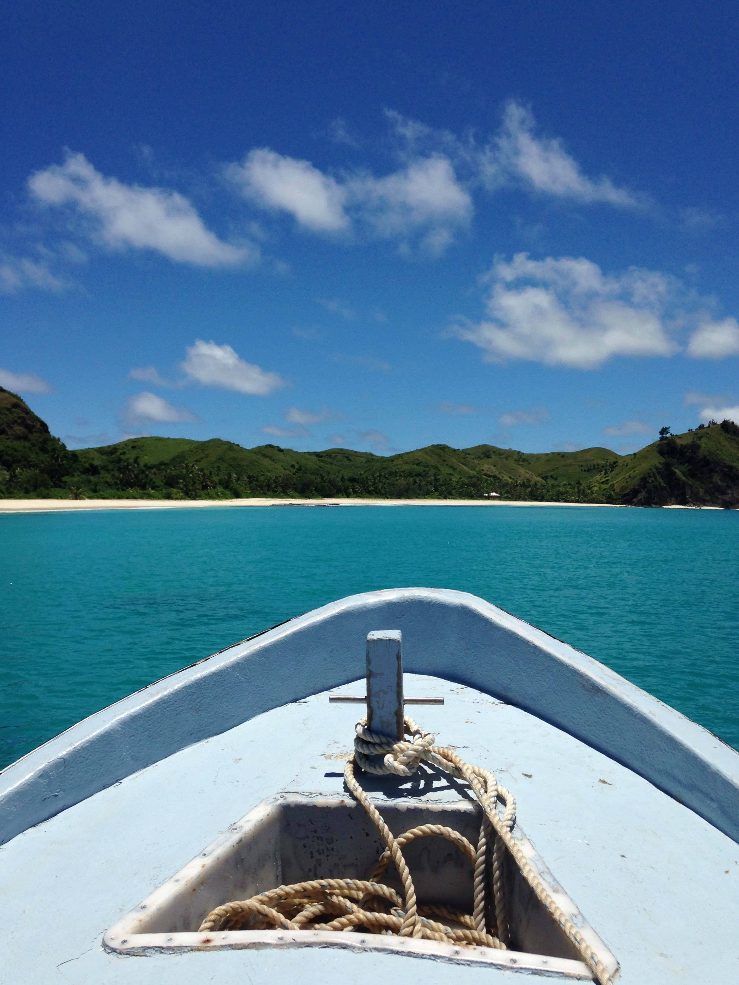 On a boat on the ocean looking back at Yasawa