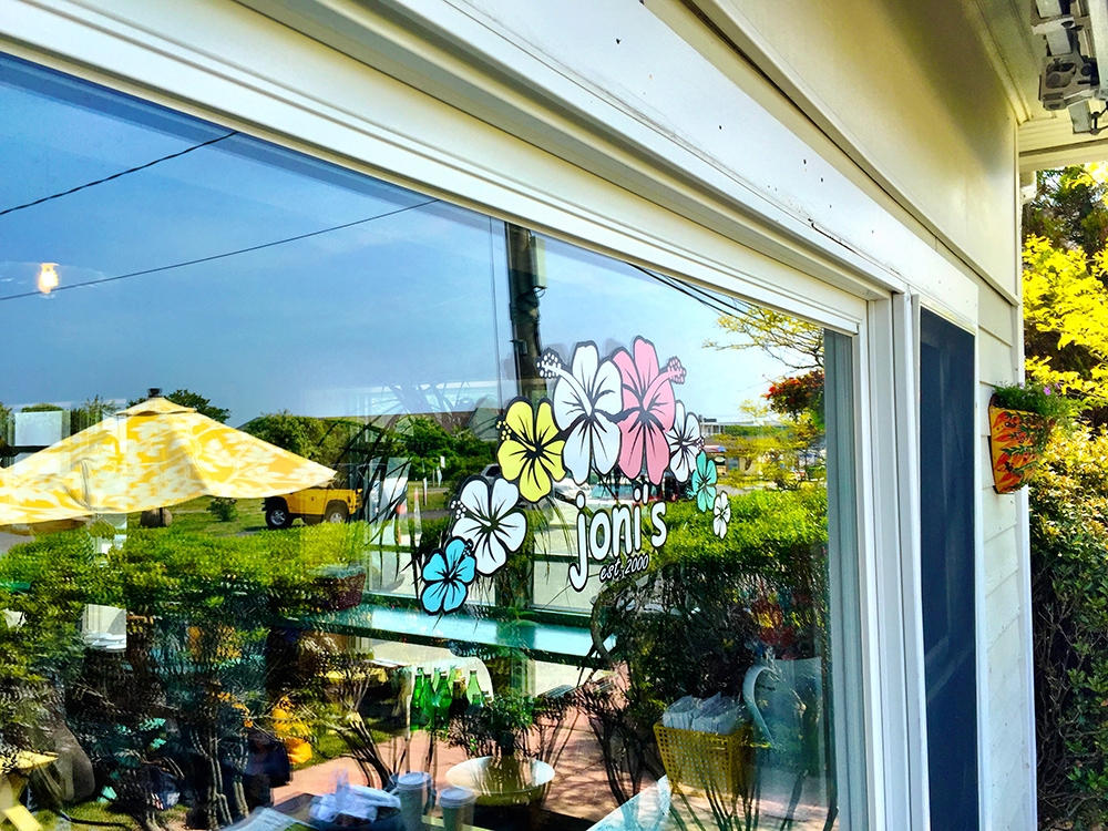 The front window at Joni's has colourful hibiscus flowers and white branding