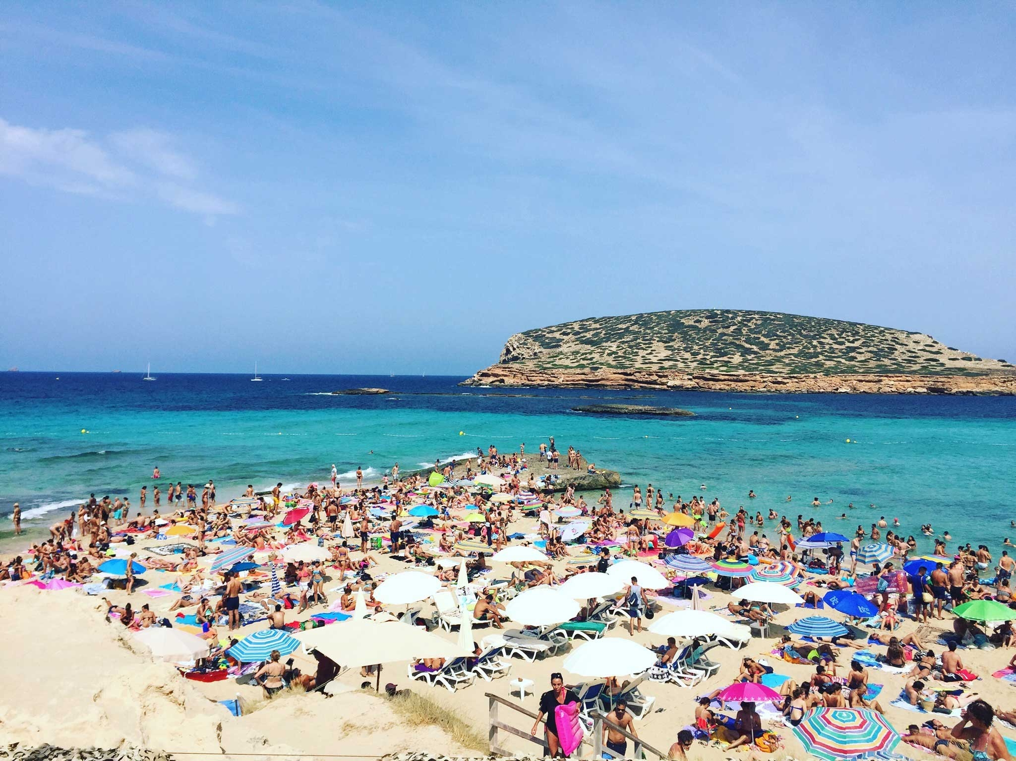 Cala Conta filled with beachgoers enjoying the clear skies and turquoise ocean