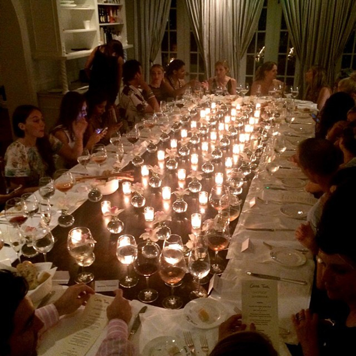 A group sits around a large rectangle dinner table that is lined with plates, wine glasses and candles