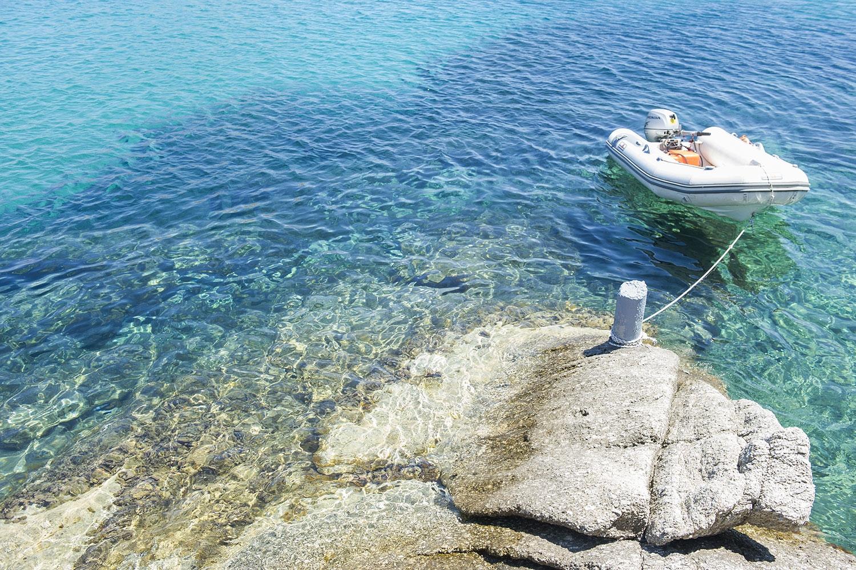 A single boat docked in a clear blue rock pool. July 2016